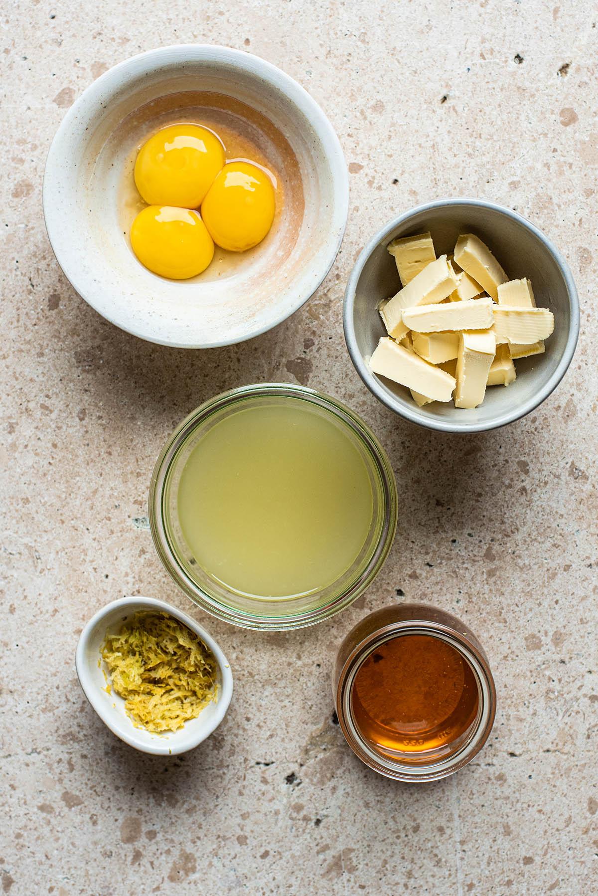 Honey lemon curd ingredients: three egg yolks, vegan butter, lemon juice, honey, and lemon zest.