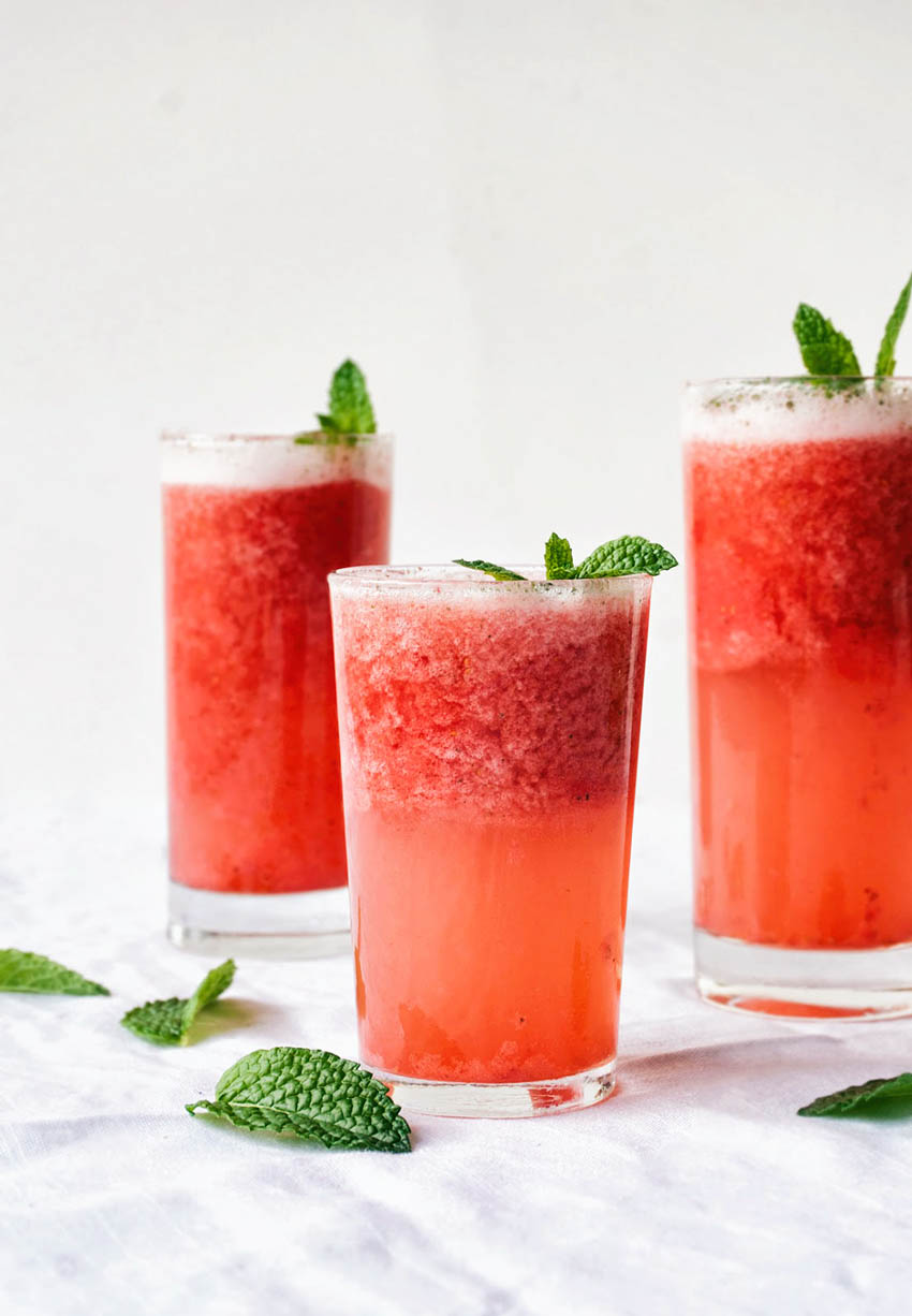 Pink strawberry slush in three glasses, topped with mint leaves on a white background.