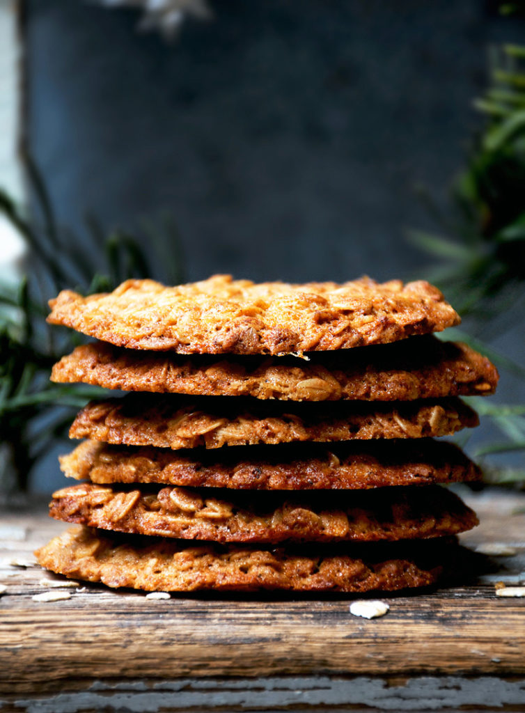Stack of large honey oat cookies on wooden board.