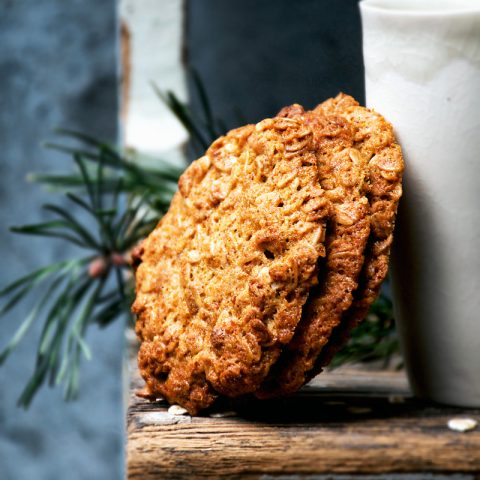 Three big honey oat cookies leaning against a white tumbler.
