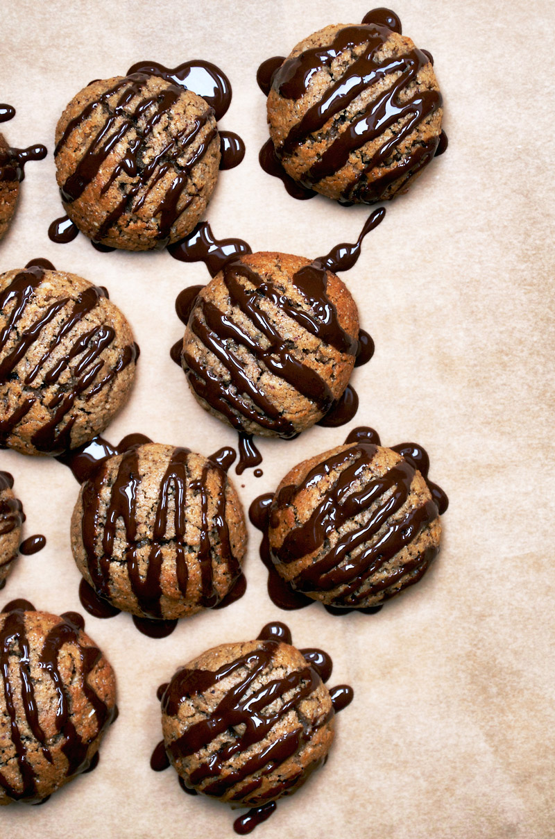 Vegan lebkuchen cookies with dark chocolate drizzle on baking paper.