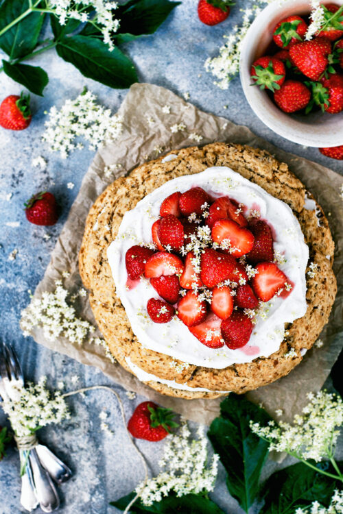 Giant scone cake layered with coconut whipped cream and strawberries, surrounded by elderflower, strawberries, and with a blue background