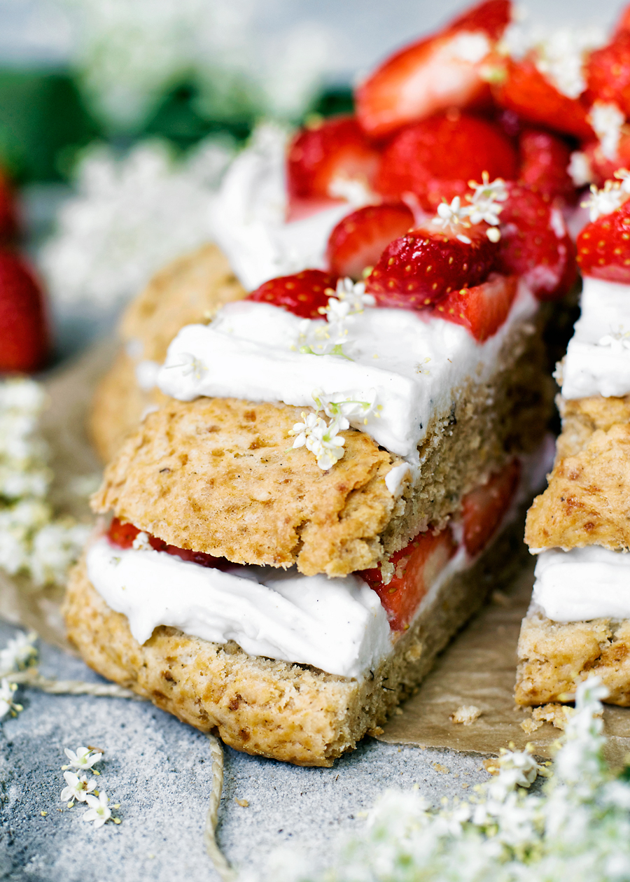 Giant vegan scone cake, front view, layered with coconut whipped cream, strawberries, and elderflower, one slice cut, close up