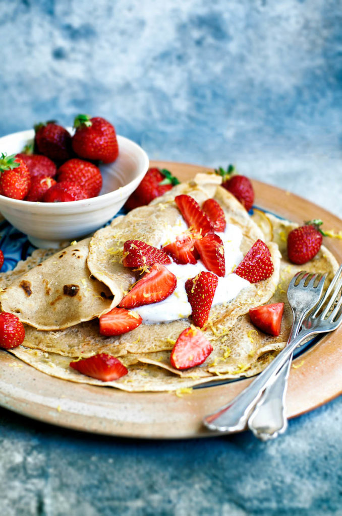 Large plate with vegan crepes, coconut yogurt, and strawberries.