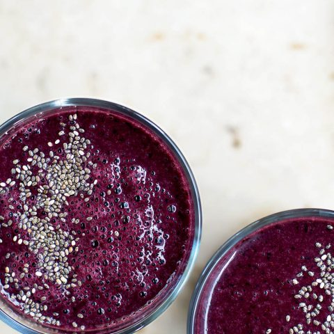 Two glasses filled with a dark purple blueberry smoothie, topped with chia seeds, top down view.
