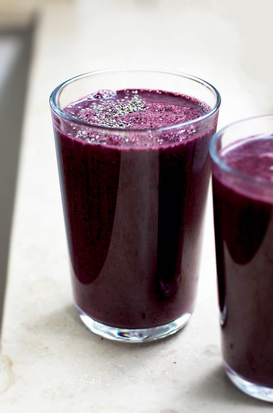 Two glasses filled with a dark purple blueberry smoothie, topped with chia seeds.
