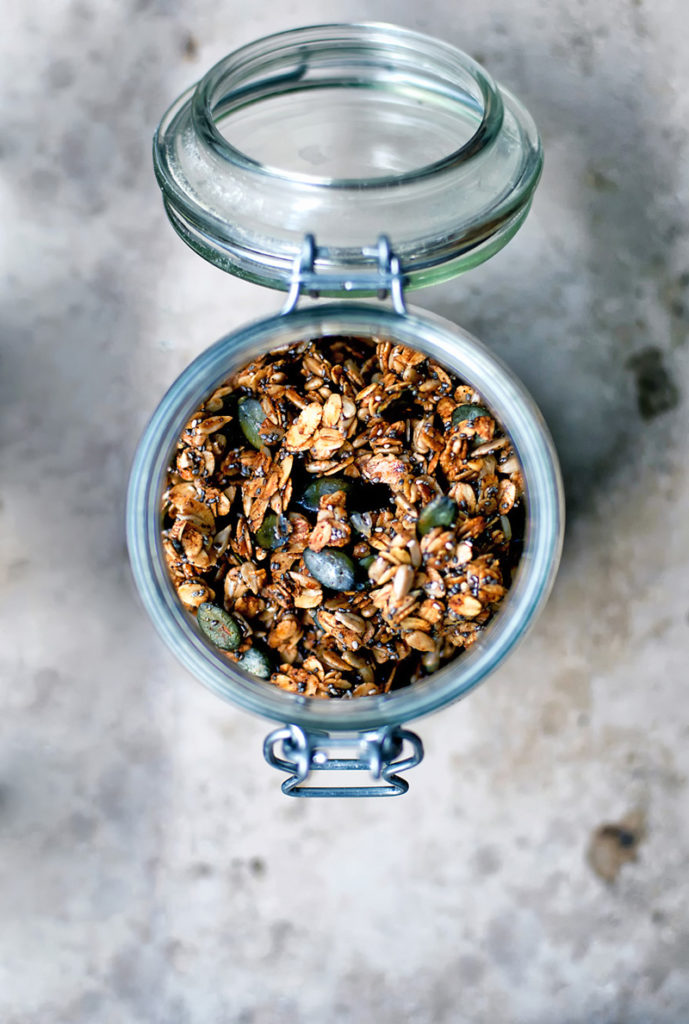 Olive oil granola with pumpkin seeds in a glass jar, top down view, on stone surface.