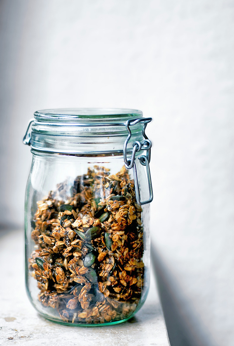 Olive oil granola with pumpkin seeds in a glass jar on stone surface.