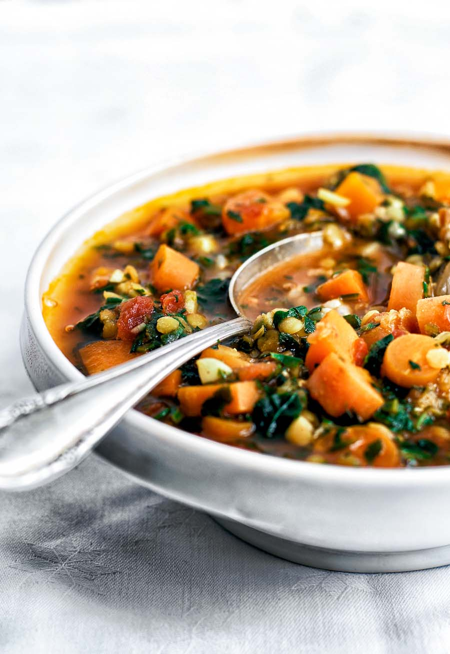 Bowl of red lentil spinach soup with rice.