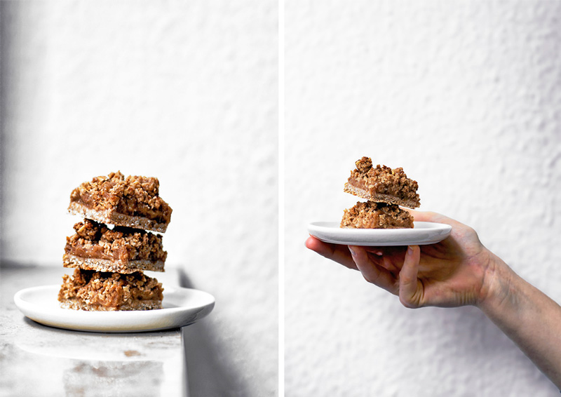 Two photos: on the left, a stack of three apple crumble bars on a white plate. On the right, a hand holding up a plate with two bars.