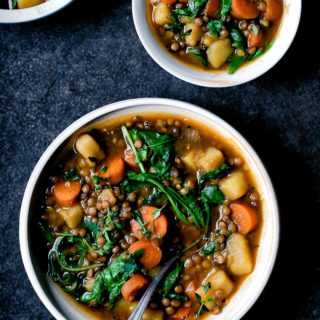 Three bowls of lentil potato stew with greens and carrots on a dark blue background.