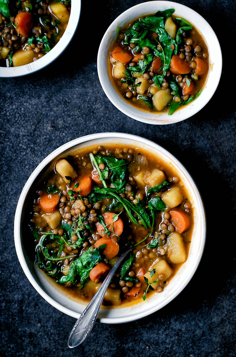 Three bowls of lentil, carrot, and potato stew.