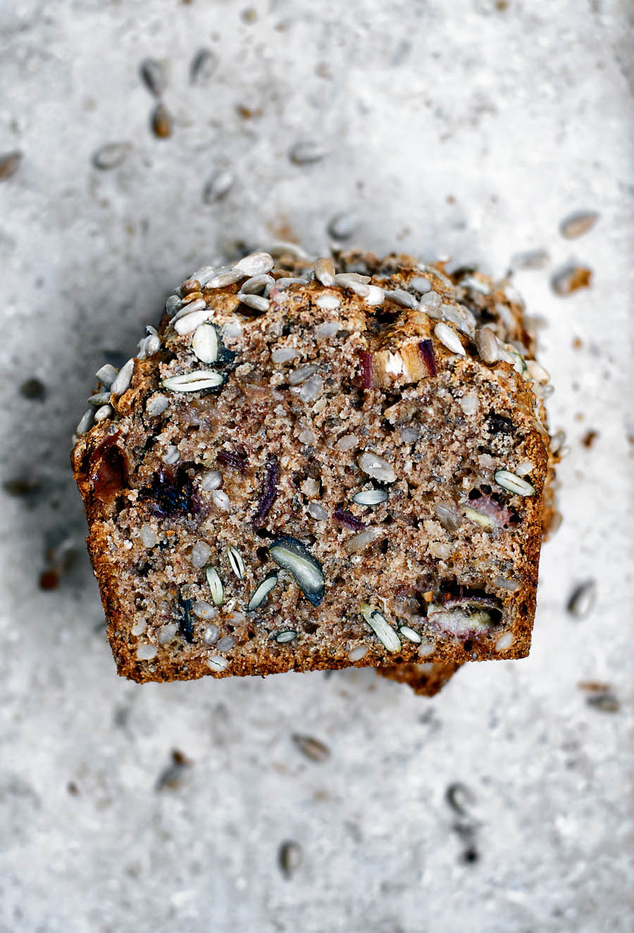 Several slices of banana bread with seeds and dates, stacked, top down view to show interior texture.