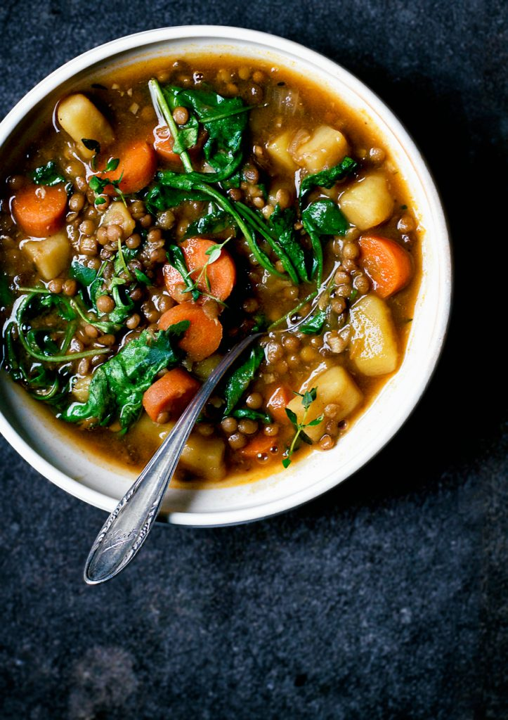 Lentil and potato stew with rucola and carrots in white bowl with spoon on dark blue background.