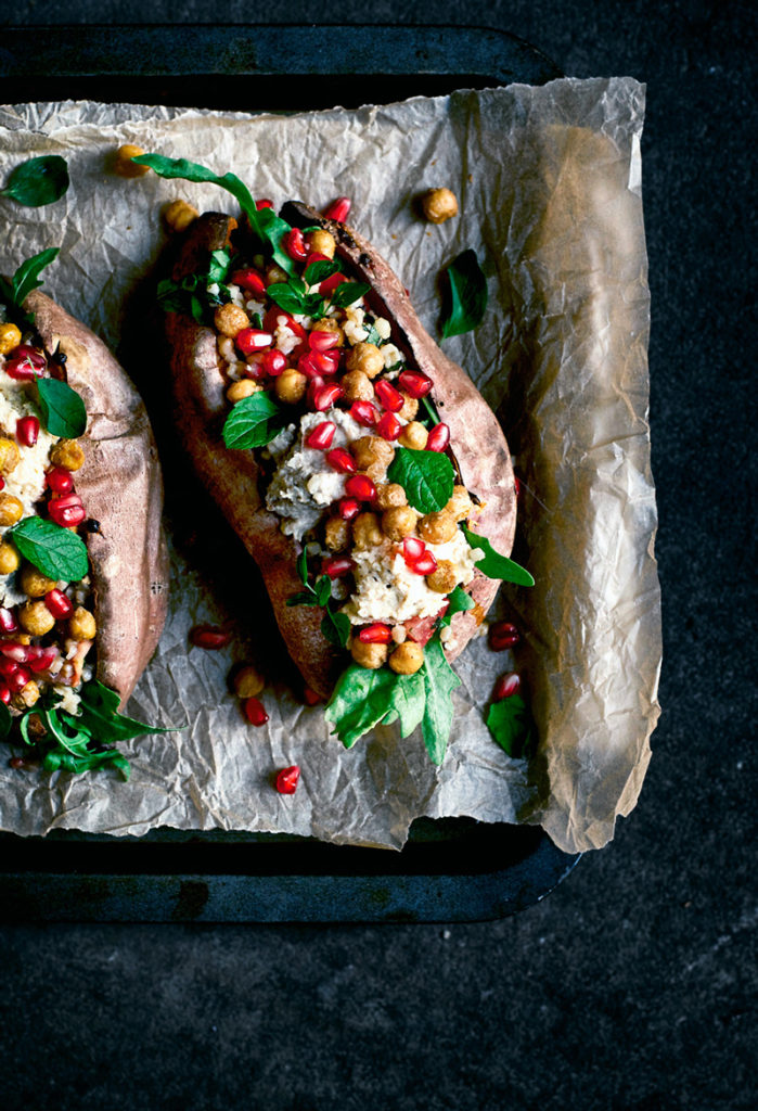Stuffed sweet potatoes with greens, hummus, chickpeas, and pomegranate on baking sheet.
