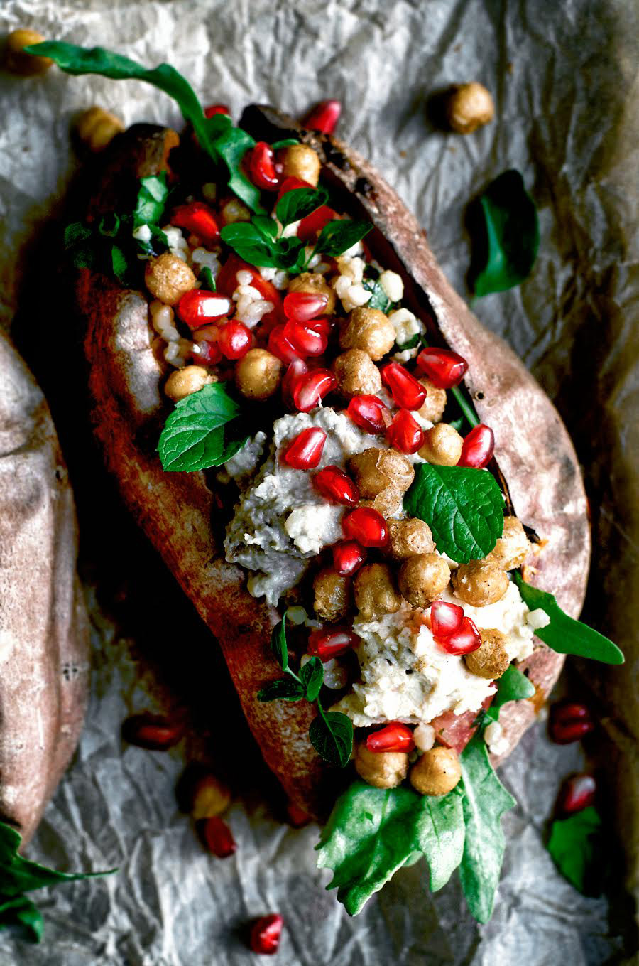 Stuffed sweet potato with greens, hummus, chickpeas, and pomegranate on baking sheet.