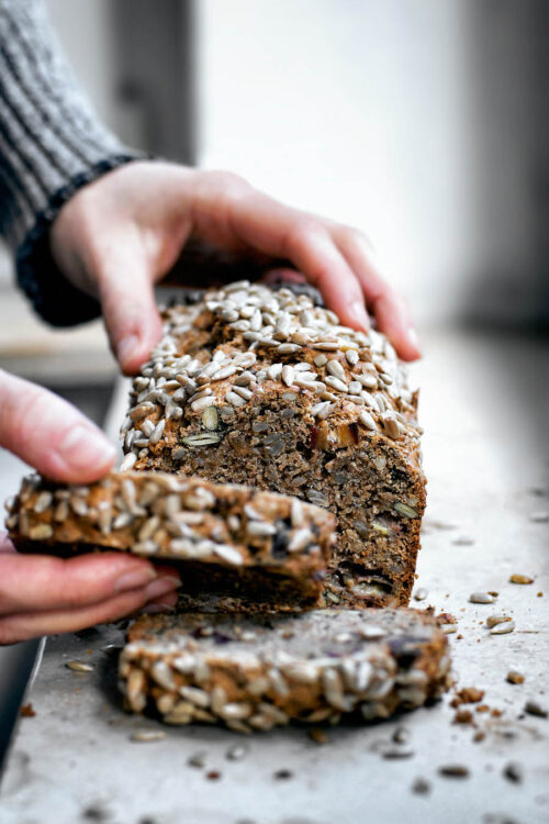 Woman's hands taking a slice of banana bread from the loaf.
