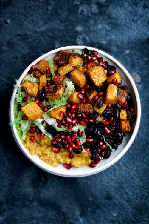 Bowl filled with black beans, turmeric rice, roasted pumpkin, cabbage salad, and pomegranate.