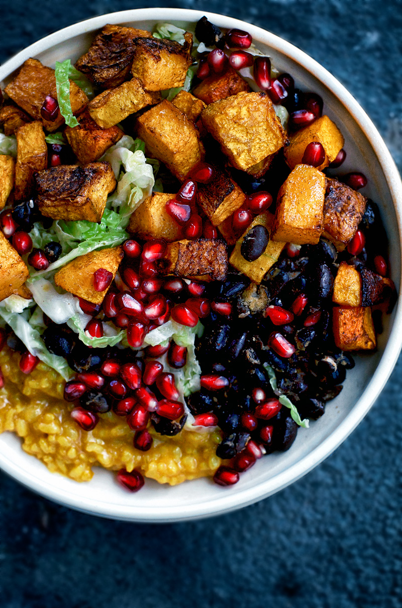 Close up of bowl filled with black beans, turmeric rice, roasted pumpkin, cabbage salad, and pomegranate.