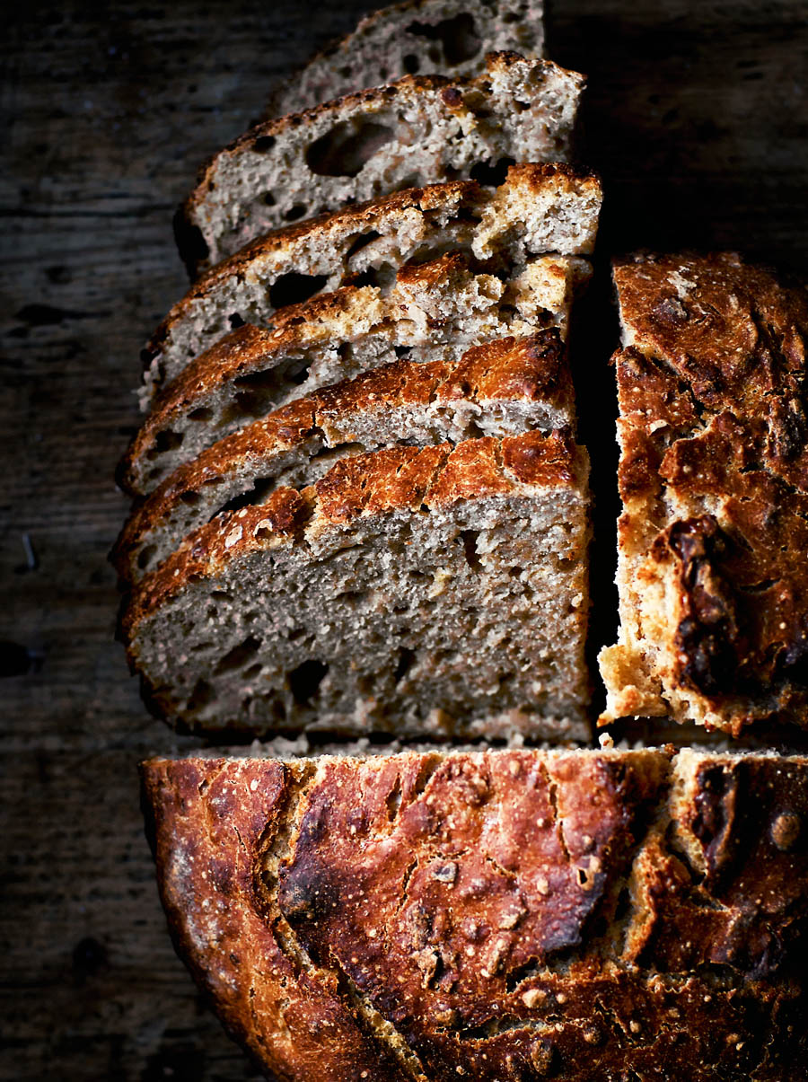 A loaf of honey oat sourdough bread with a quarter of it sliced, close up.