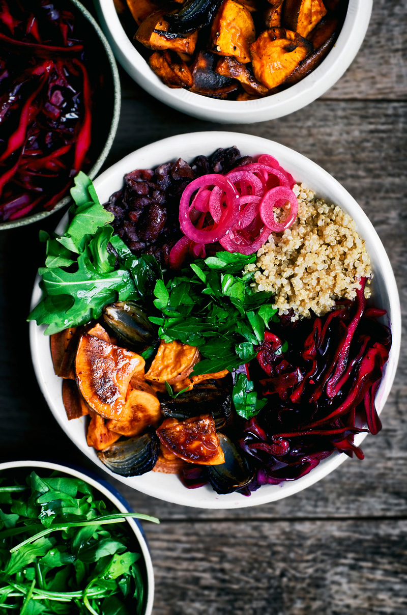 Winter energy bowl with quinoa, red cabbage, roasted sweet potato, and pickled onions.
