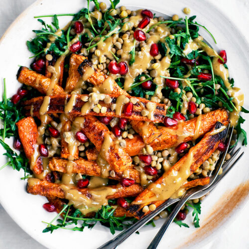 Roasted carrot lentil salad with arugula and tahini sauce on white plate.