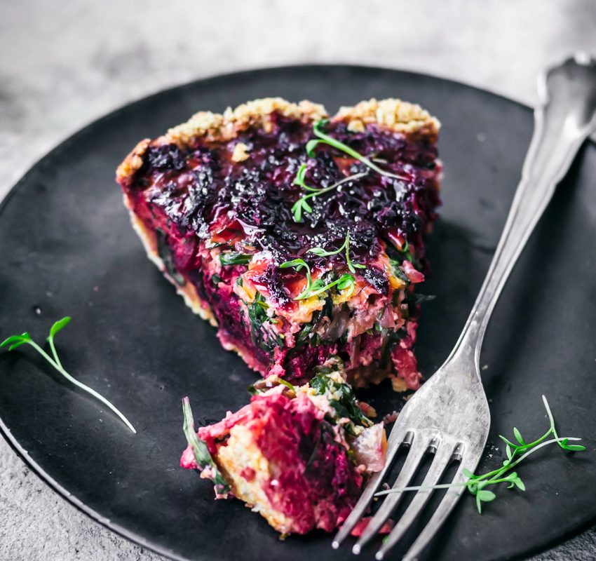 Beet tart slice on black plate, with fork and one bite cut