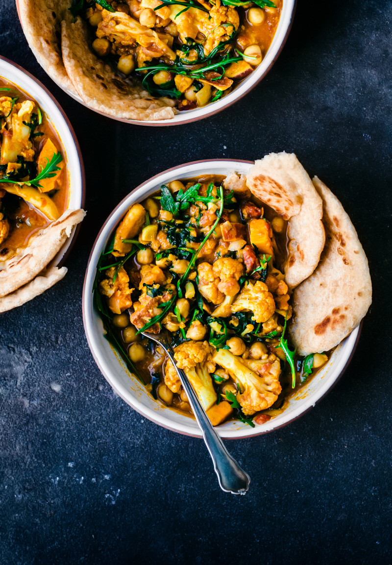 Three bowls of cauliflower sweet potato curry with naan on dark background.
