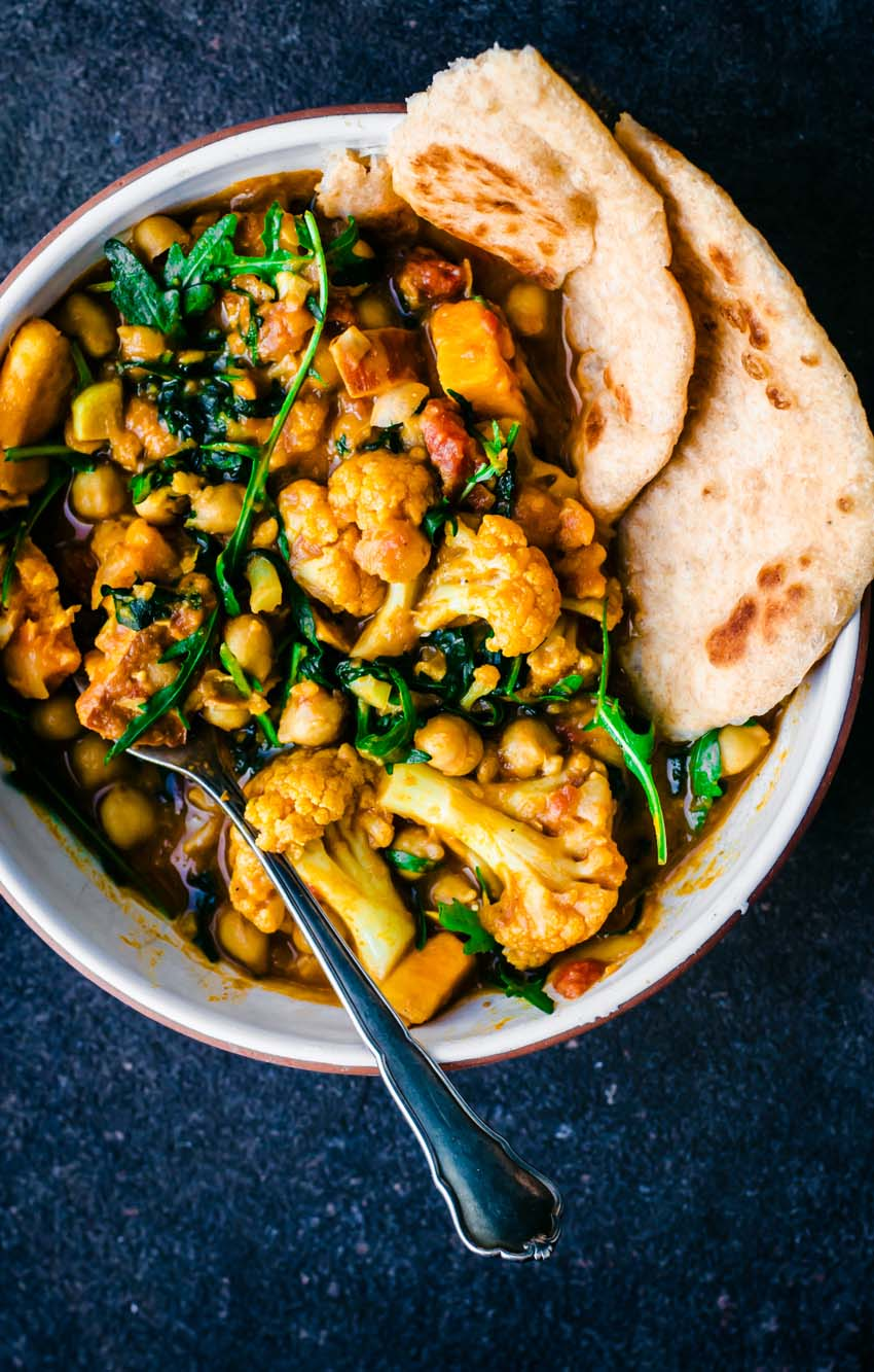 Bowl of cauliflower sweet potato curry with naan on dark background.