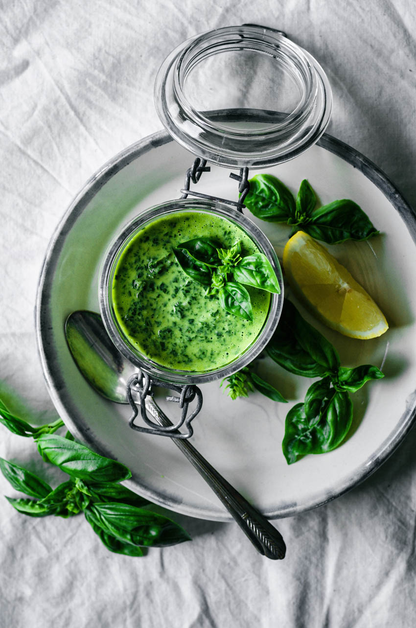 Top down view of basil in a jar with lemon, basil, and a spoon.