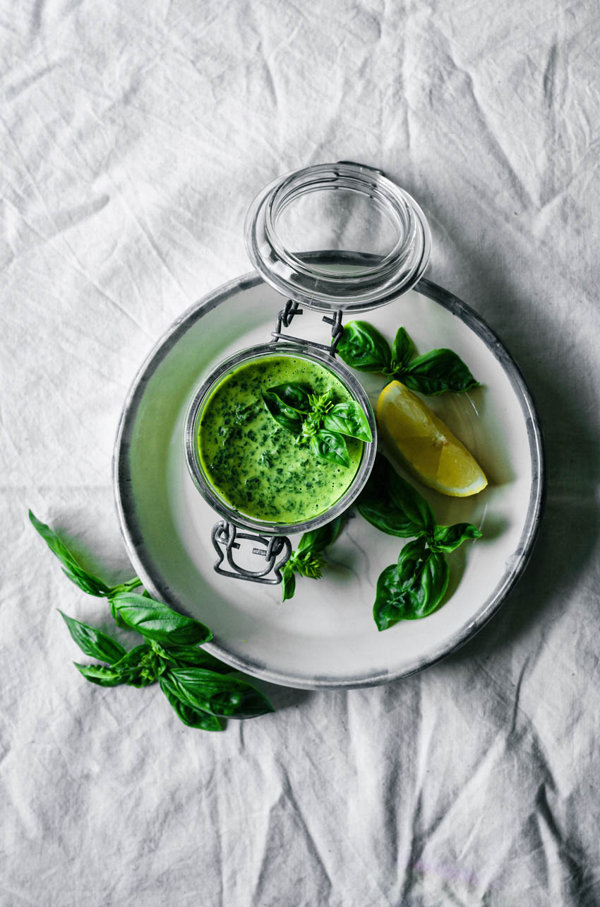 Top down view of basil in a jar with lemon and basil leaves.