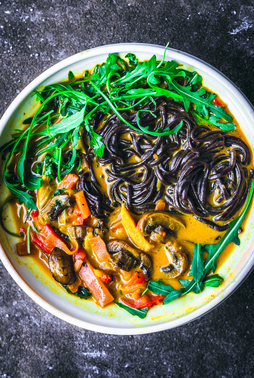 Close up of a vegan yellow curry with vegetables and black rice noodles.