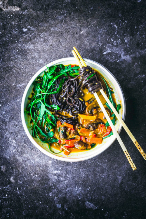 A vegetable noodle curry in a white bowl with chopsticks.