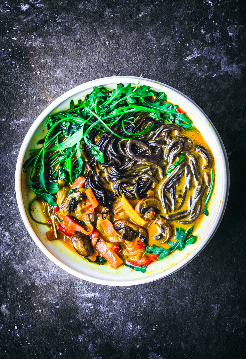 An orange curry sauce with black noodles and vegetables.