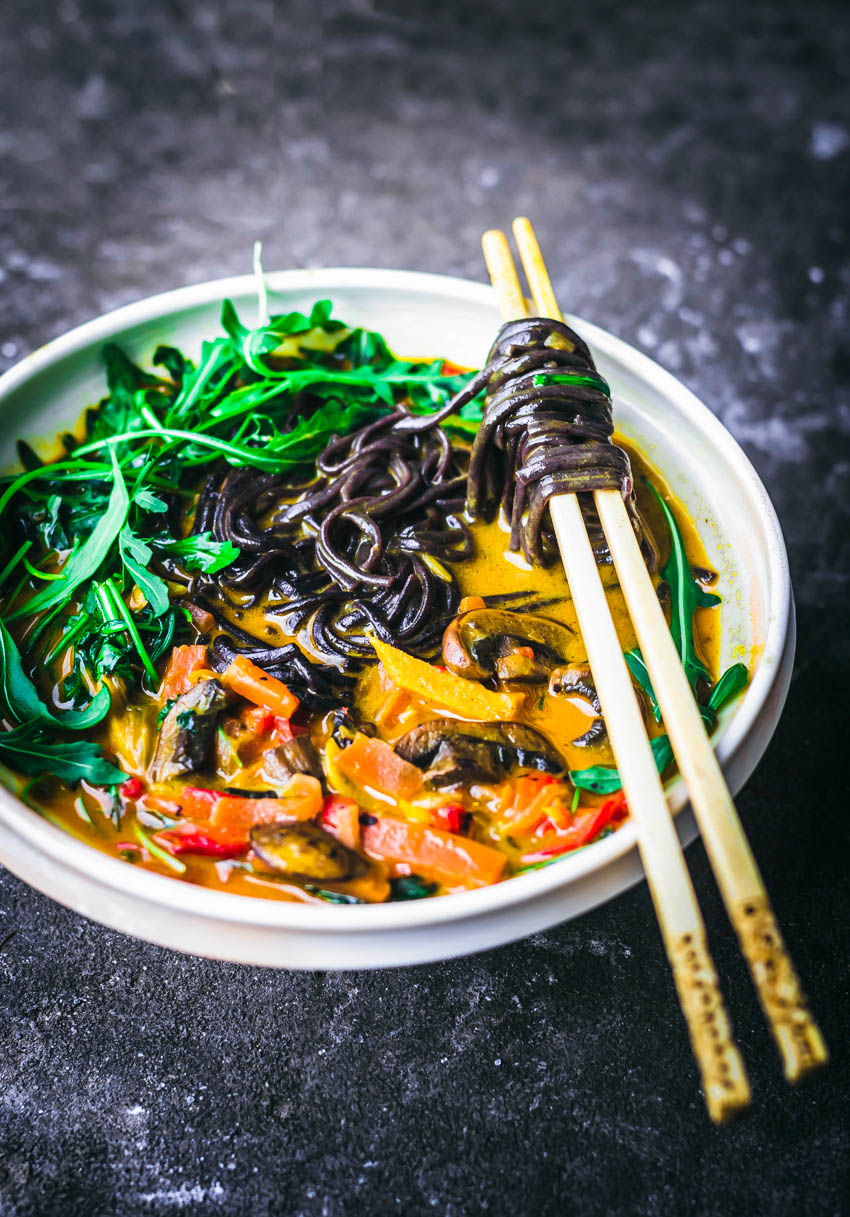A bowl of yellow curry with black rice noodles on chopsticks.
