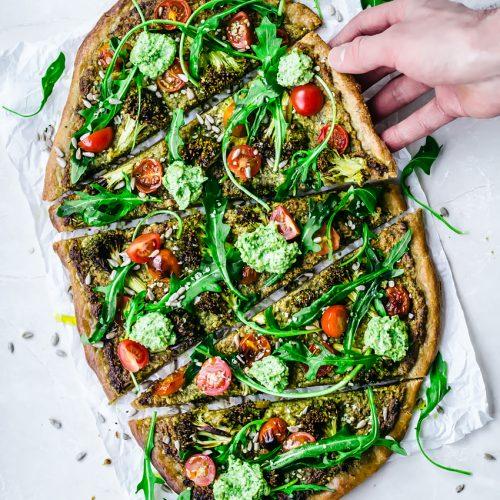 Vegan pesto vegetable pizza with broccoli and cherry tomatoes
