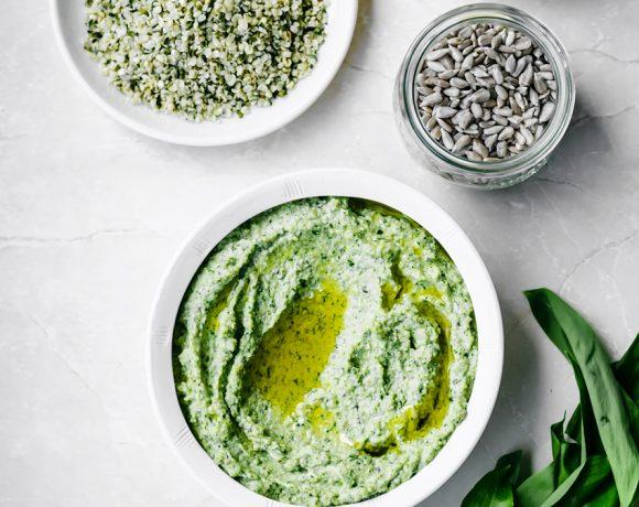 Light green wild garlic pesto in bowl with hemp, sunflower seeds, lemons, and wild garlic surrounding