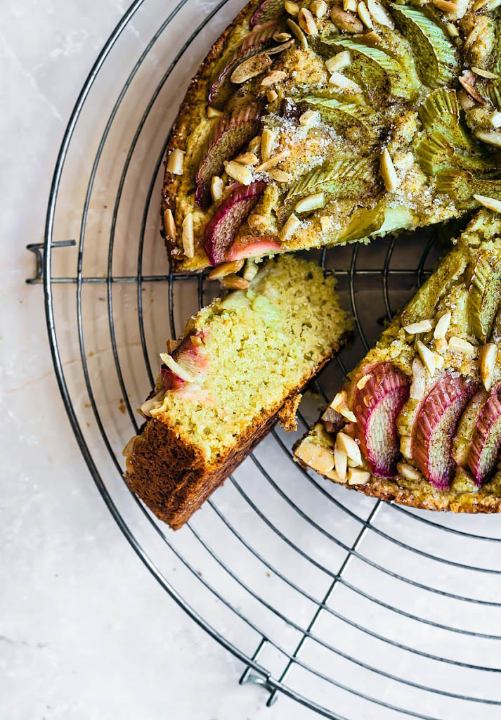 Almond rhubarb cake with a slice cut and turned on its side.