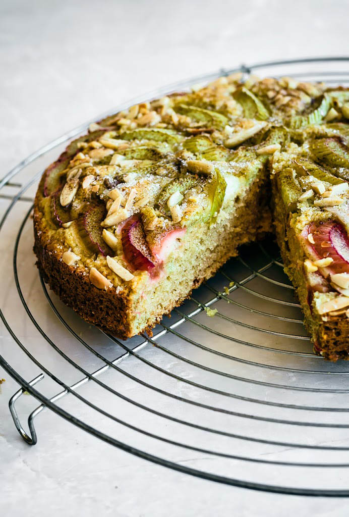 Rhubarb topped cake with a slice removed to show interior crumb.