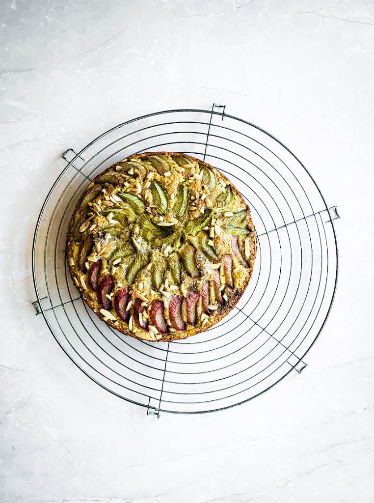 Almond rhubarb cake on a large round metal cooling rack.