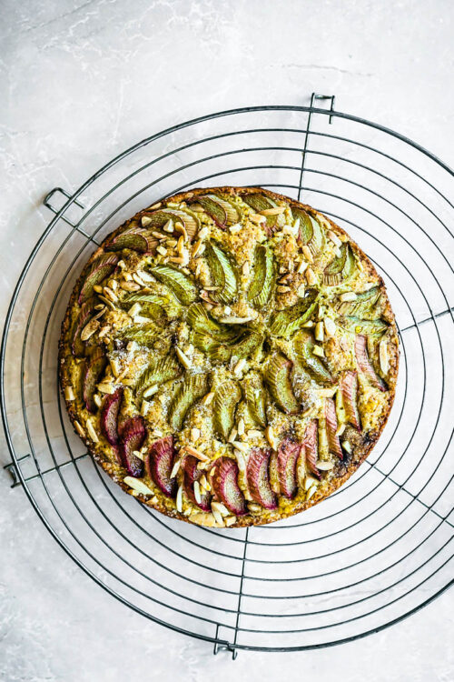 Rhubarb topped cake on a large round metal cooling rack.