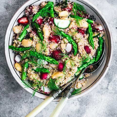 Strawberry, radish, cucumber, and asparagus quinoa salad in large bowl.