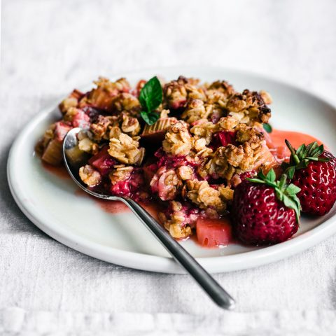 Strawberry rhubarb crisp on plate with fresh berries.