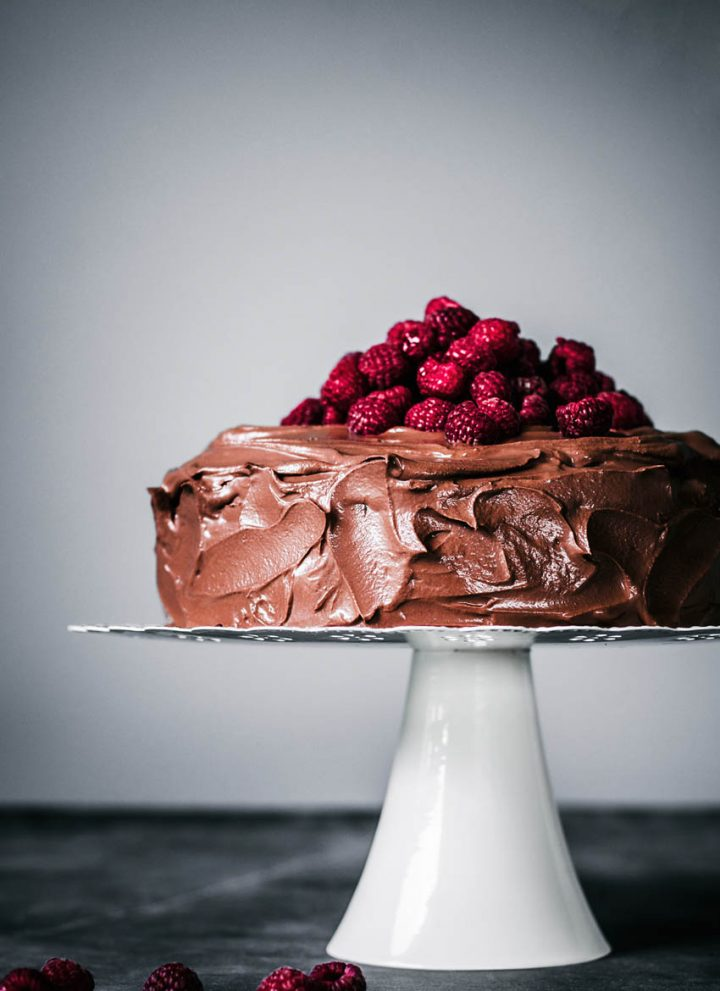 Chocolate ganache covered cake topped with fresh raspberries on a cake stand.