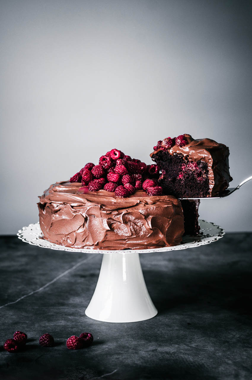 Chocolate raspberry cake with a slice cut and being lifted from the cake.