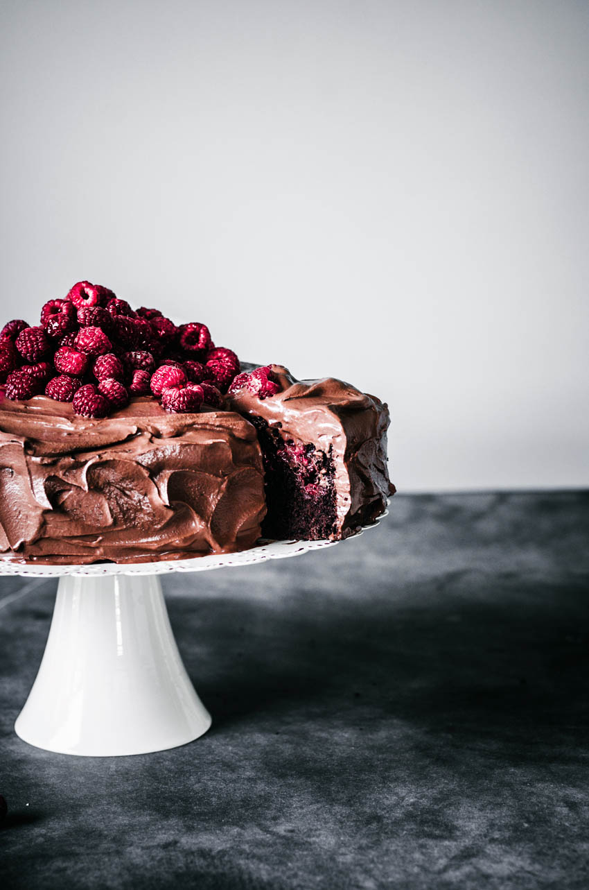 Chocolate raspberry cake on a stand with a slice cut and partly out.