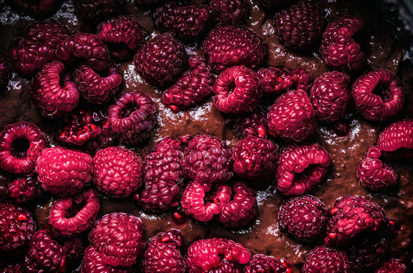 Close up of chocolate cake batter with fresh raspberries.