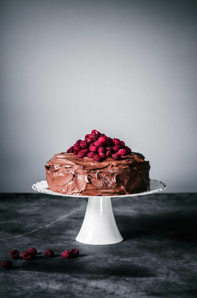 Chocolate raspberry cake on white cake stand.