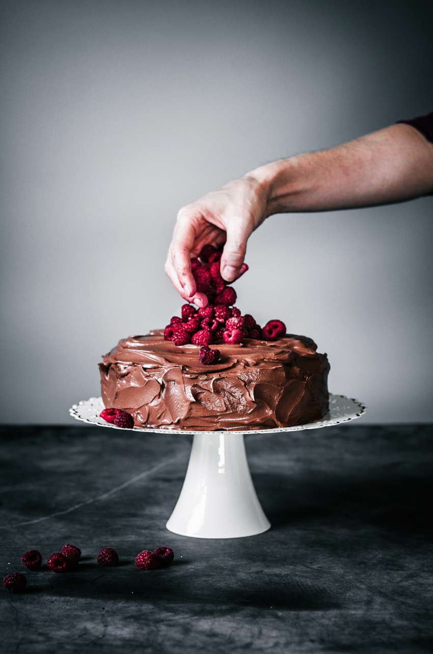 Chocolate ganache iced cake on white cake stand with someone dropping raspberries onto the top of the cake.