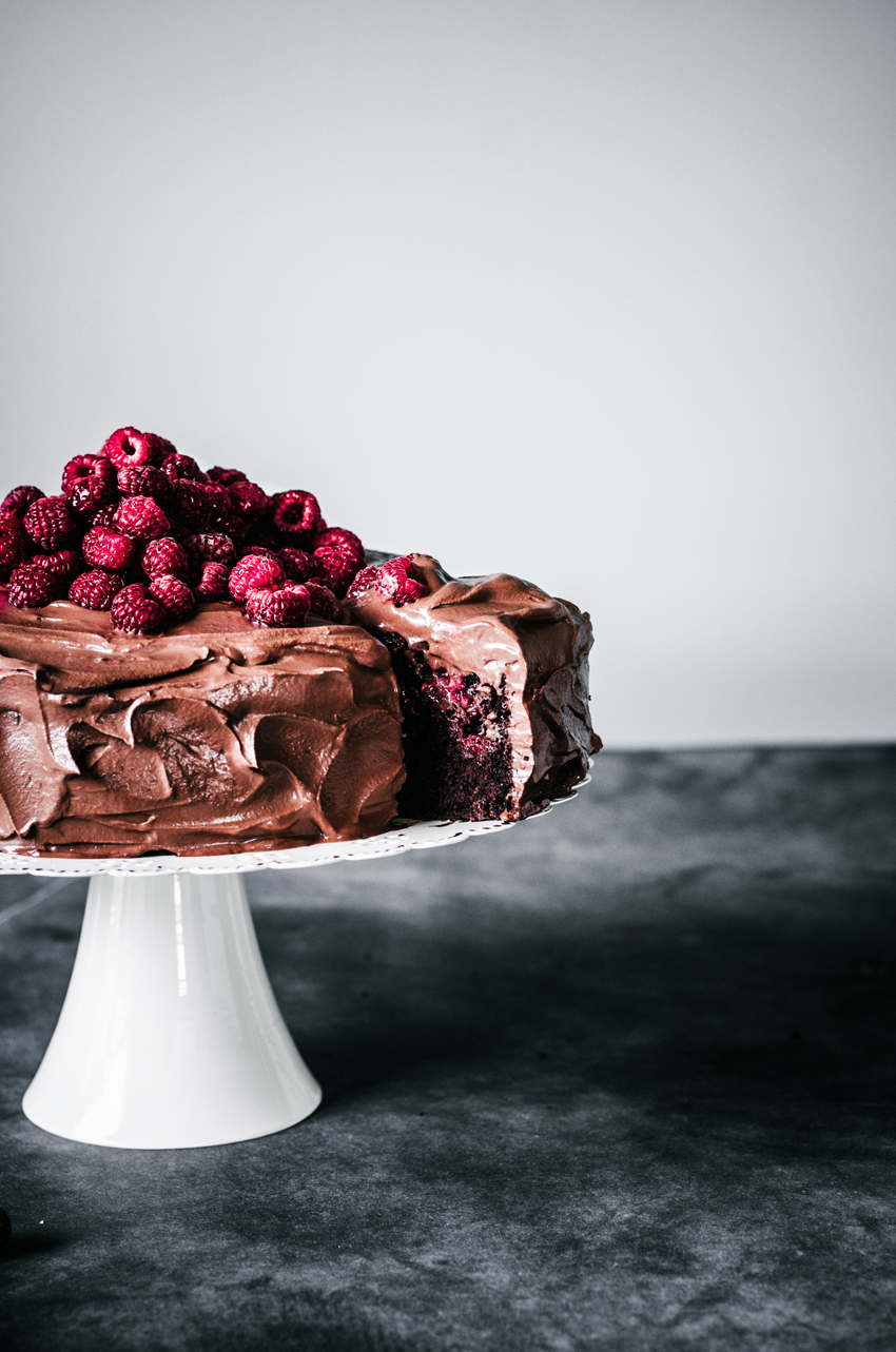Chocolate ganache iced cake on white cake stand with pile of raspberries on top, one slice cut and peeking out from cake.